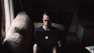 man sitting with a laptop in a dark room wondering why his excuses make him unhappy