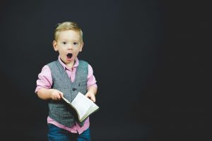 Little boy holding a book looking surprised at how to figure out what you want from your life