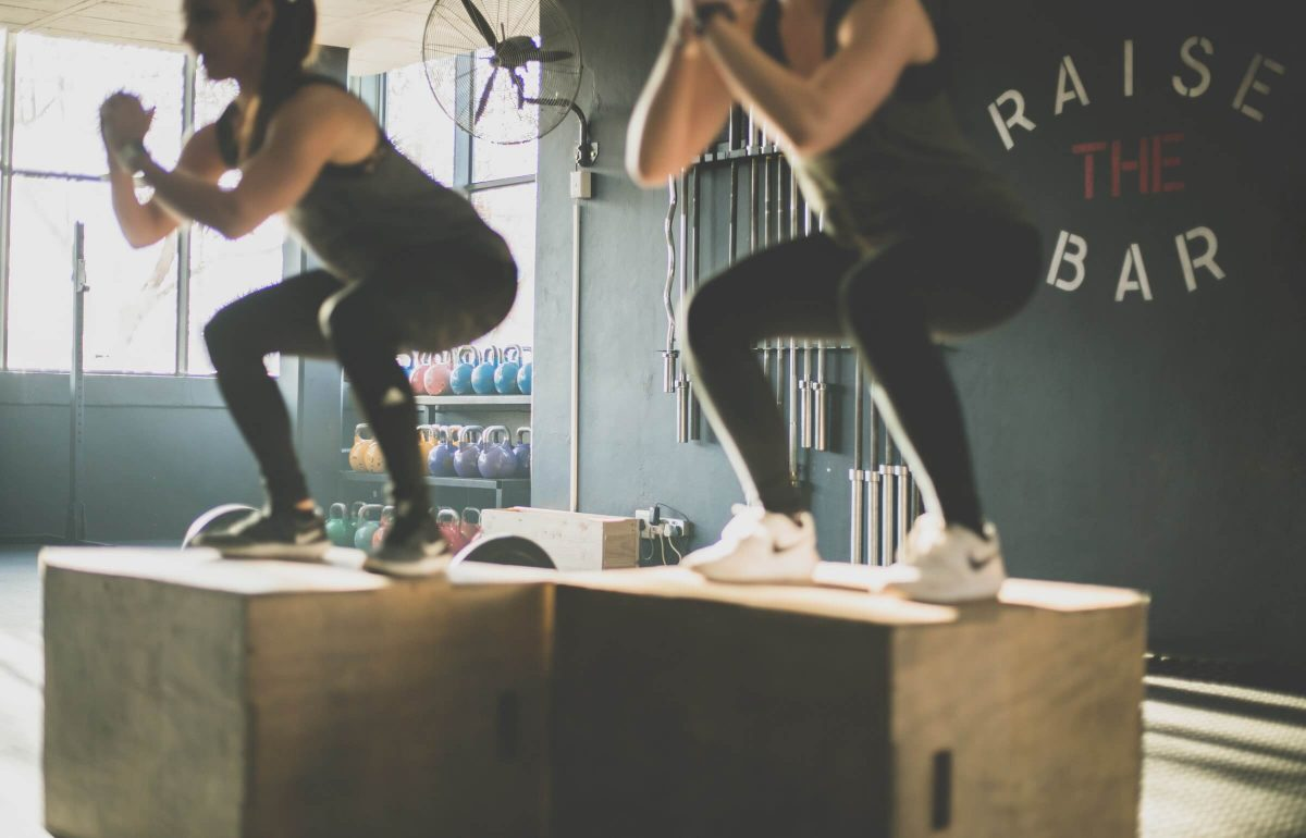 two women jumping on blocks 'raise the bar' in the background showing their kaizen mindset